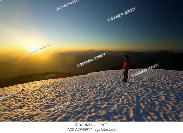 A lone mountain climber stands atop King's Peak and enjoys the last rays of the setting sun, Strathcona Park, Central Vancouver Island, British Columbia, Canada