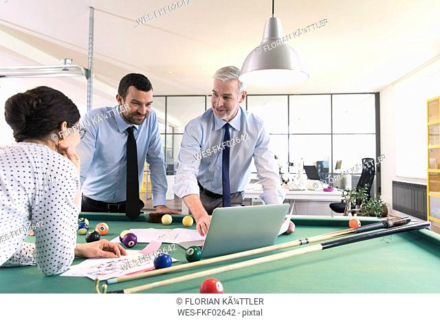 Business people standing at pool table with laptop, discussing investment strategy