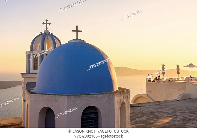 Sunset over a blue domed church and balcony on Santorini Island, Cyclades, Greece