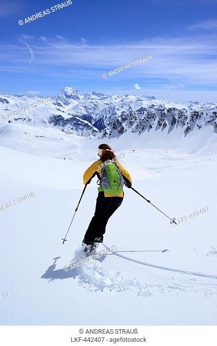 Female backcountry skier downhill skiing, Vallatscha, Sesvenna range, Ortler in background, Ofenpass, Grisons, Switzerland
