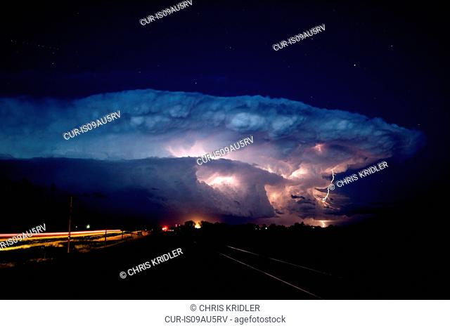 A rotating supercell storm lights up with lightning as stars shine overhead, Near Sidney, Nebraska, USA