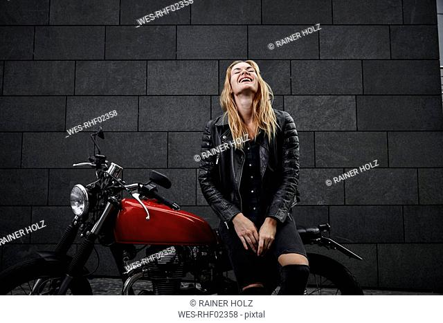 Portrait of laughing young woman with motorcycle