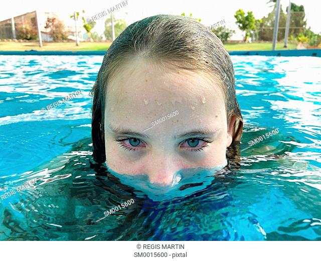 Portrait of a half submerged girl in a swimming pool