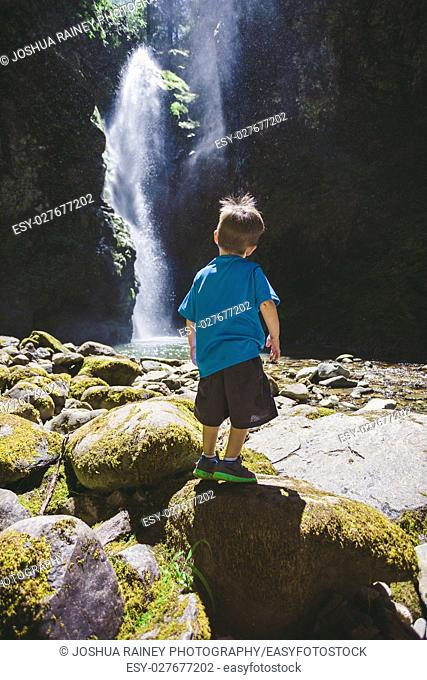 Three year old boy standing at the base of a large waterfall in the Umpqua National Forest in Oregon