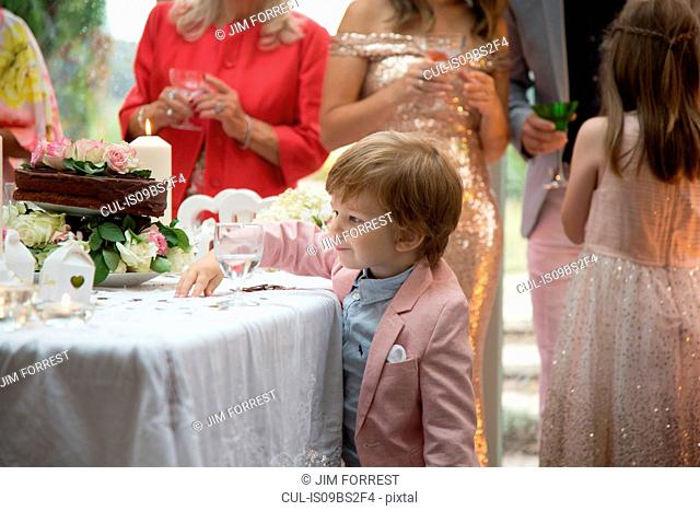 Boy curious about gifts and cake at wedding reception