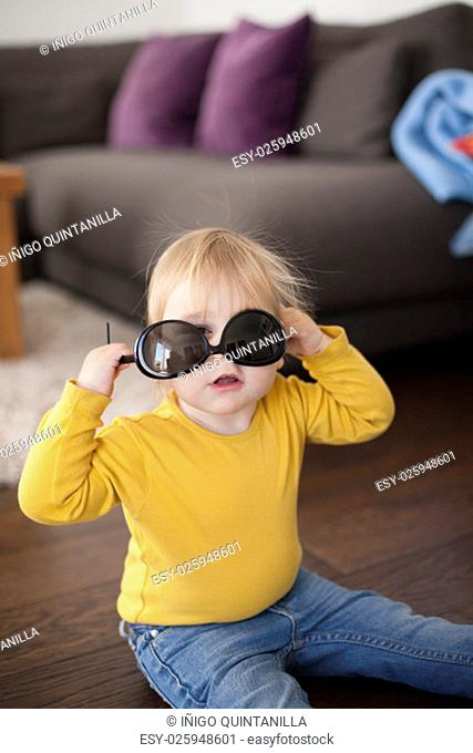 two years aged blonde happy baby yellow shirt and blue jeans playing with black sunglasses of woman mother sitting on wooden indoor floor and looking at camera
