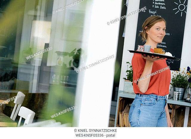 Young woman serving coffee and cake in a cafe