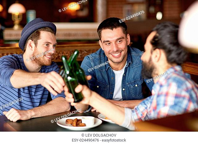 people, leisure, friendship and party concept - happy male friends drinking bottled beer at bar or pub and clinking bottles