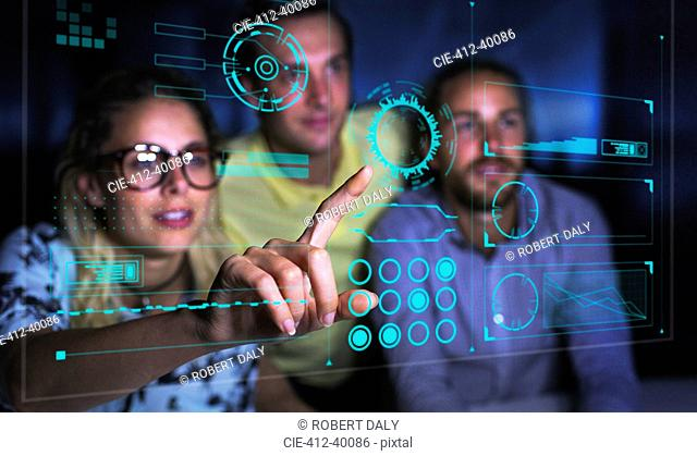 Computer programmers examining data on futuristic hologram