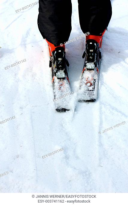 Legs of a skier with black ski pants and red ski boots on the slopes, seen from behind