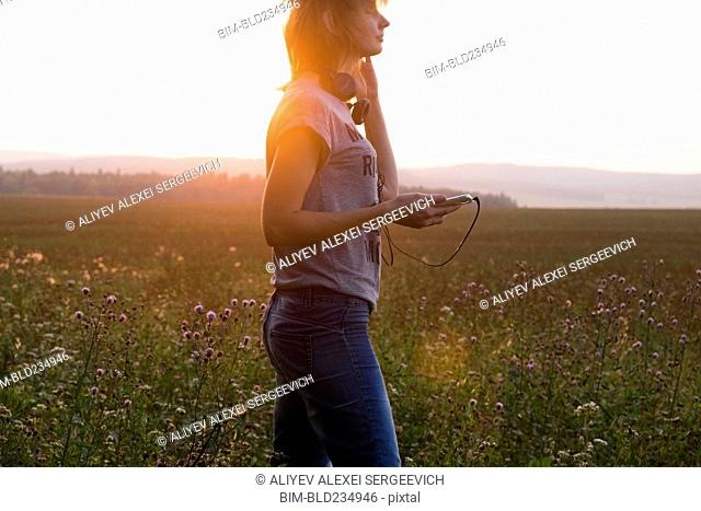 Caucasian woman holding cell phone standing in field