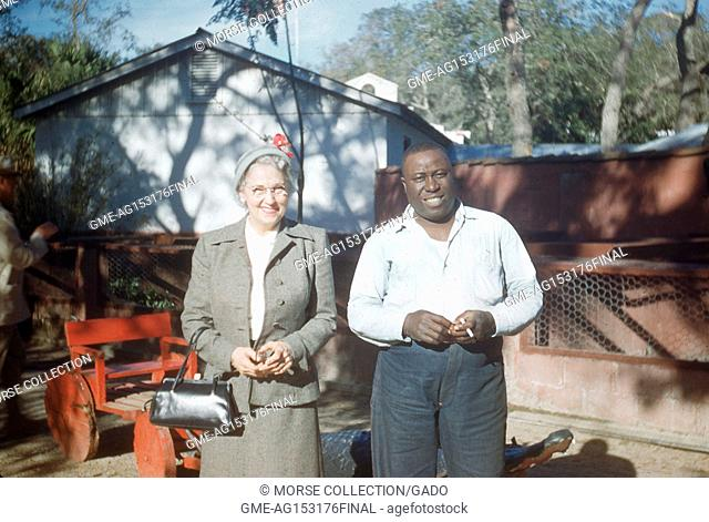 Portrait of a white woman and a black man smiling together for the camera, posing outside a barn in Natchez, Mississippi, June, 1953. ()