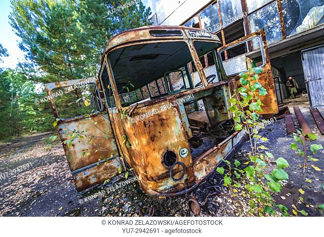 Rusty bus in front of abandoned Jupiter Factory in Pripyat ghost town of Chernobyl Nuclear Power Plant Zone of Alienation in Ukraine