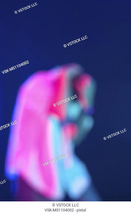 Blurred figure covering head