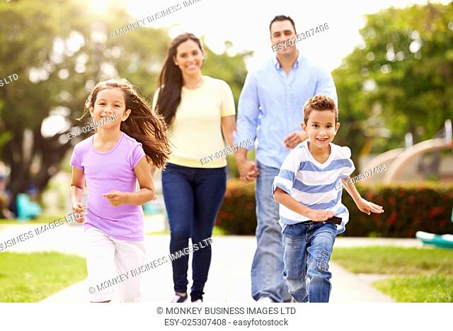 Hispanic Family Walking In Park Together
