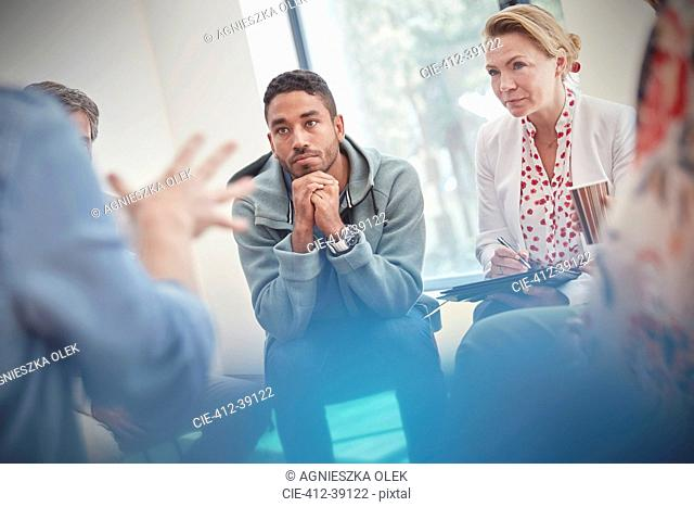 Attentive man and woman listening in group therapy session