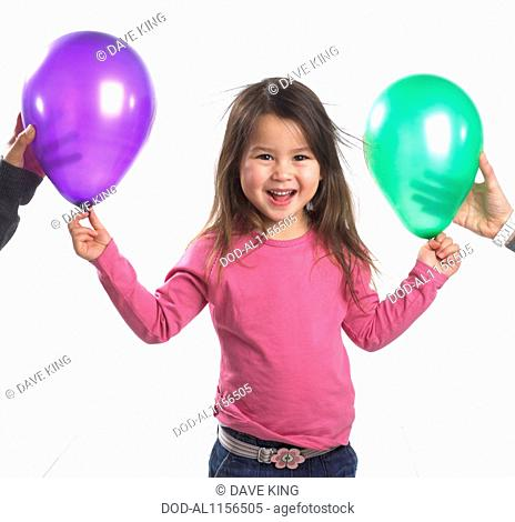Girl (3.5 years) standing laughing as her hair sticks with static electricity to two balloons