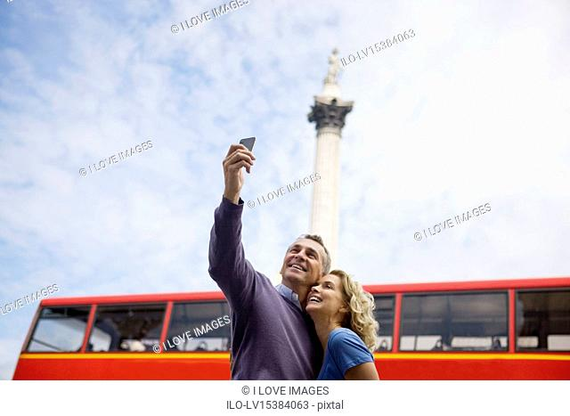 A middle-aged couple taking a photograph of themselves in front of Nelson's column
