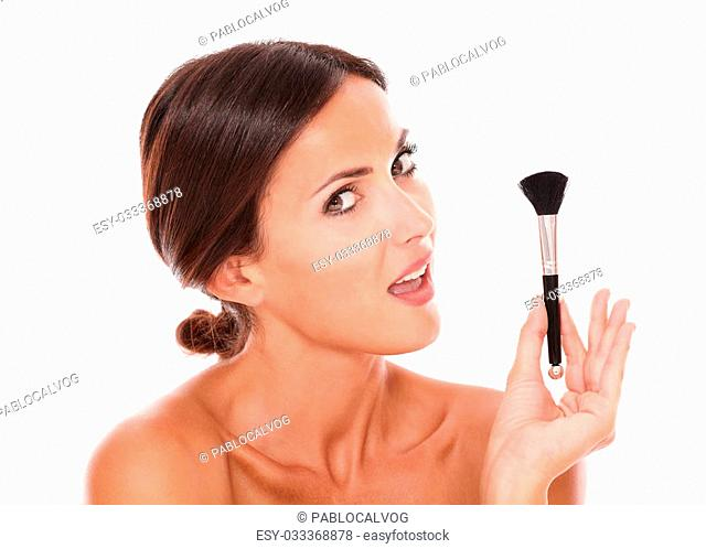 Stylized portrait of beautiful young woman with make up brush for pampering her face and nude shoulders while looking at camera on isolated white background
