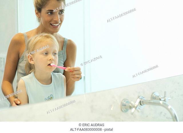 Mother helping daughter brush her teeth