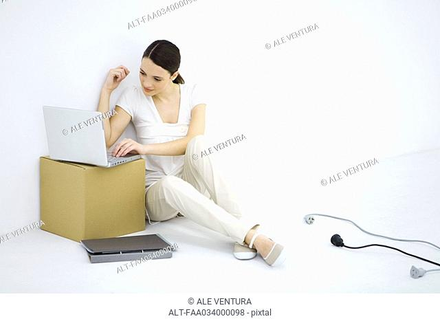 Woman sitting on floor, using laptop computer set on cardboard box