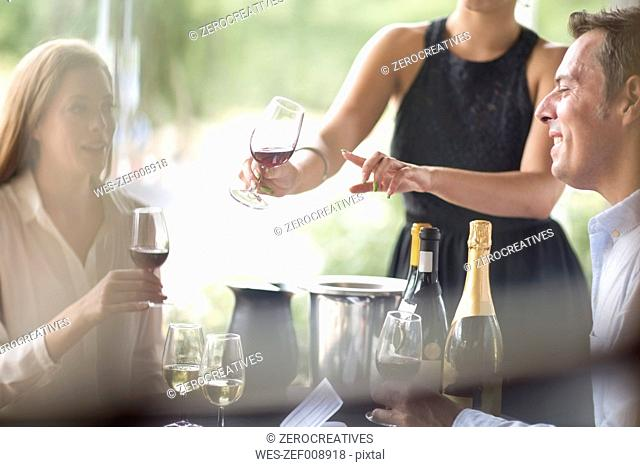 Waitress in restaurant presenting red wine