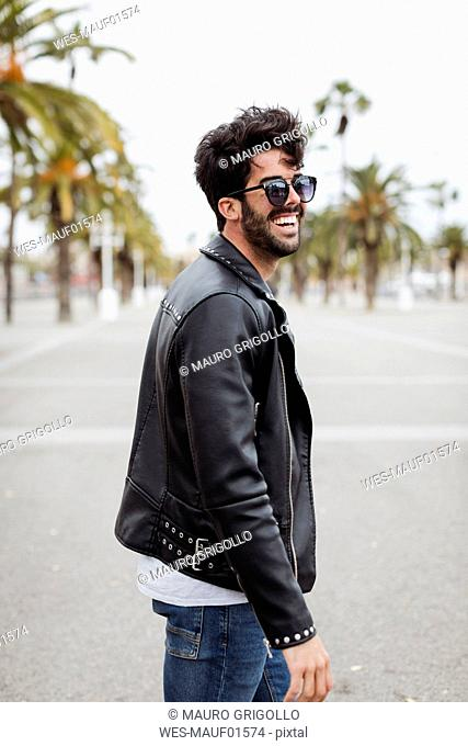 Spain, Barcelona, happy young man on promenade with palms