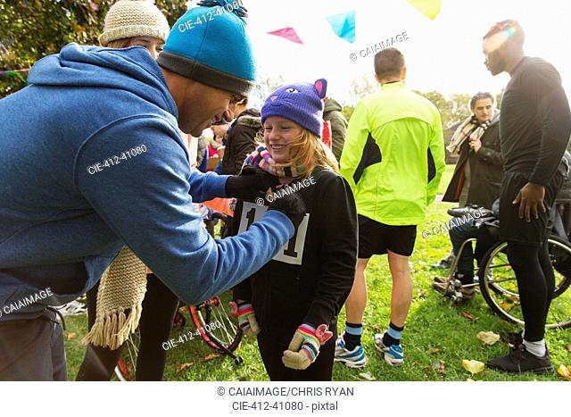 Father pinning marathon bib on daughter at charity run in park