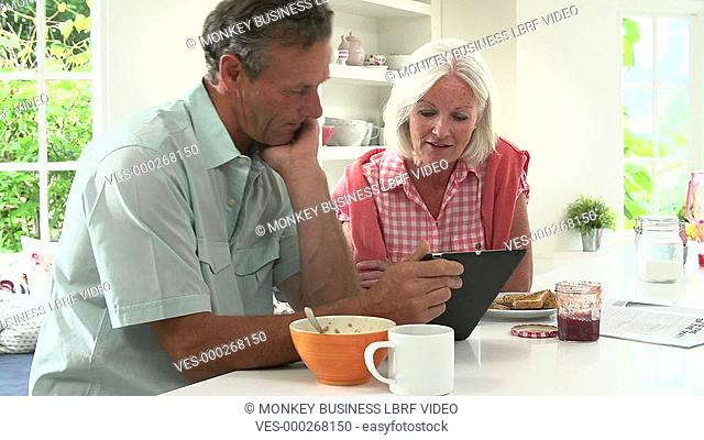 Middle aged couple talking together and using digital tablet over breakfast. Shot on Sony FS700 in PAL format at a frame rate of 25fps