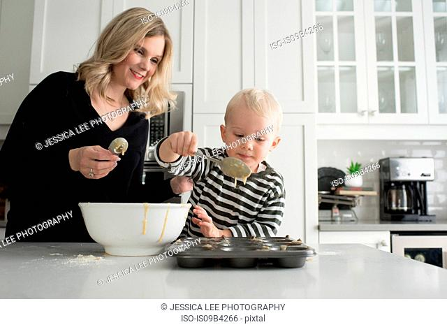 Mother and son baking together, putting mixture into baking tray
