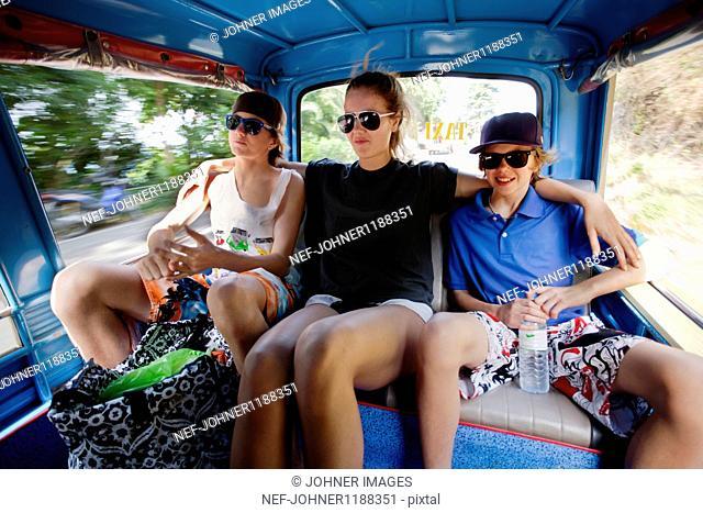 Three teenagers riding in rickshaw