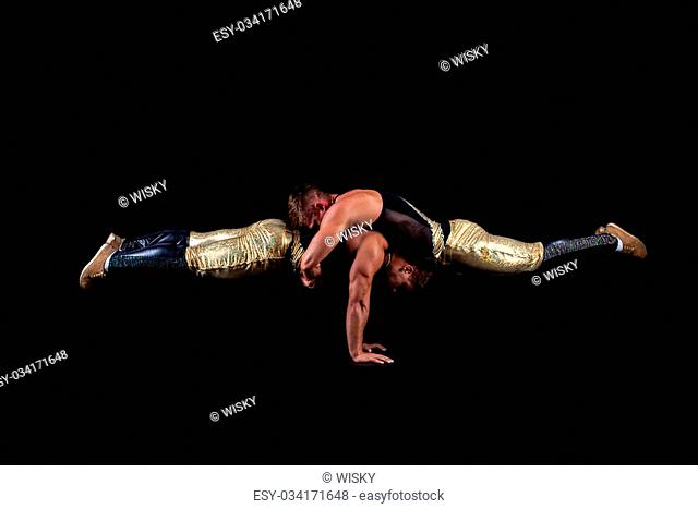 Sexy acrobats balancing in studio, isolated on black background