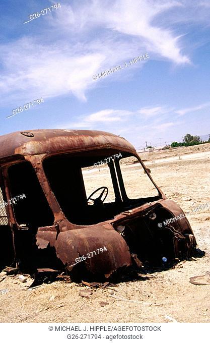 Sunken bus in salt covered ground. Bombay Beach along the Salton Sea. California. USA