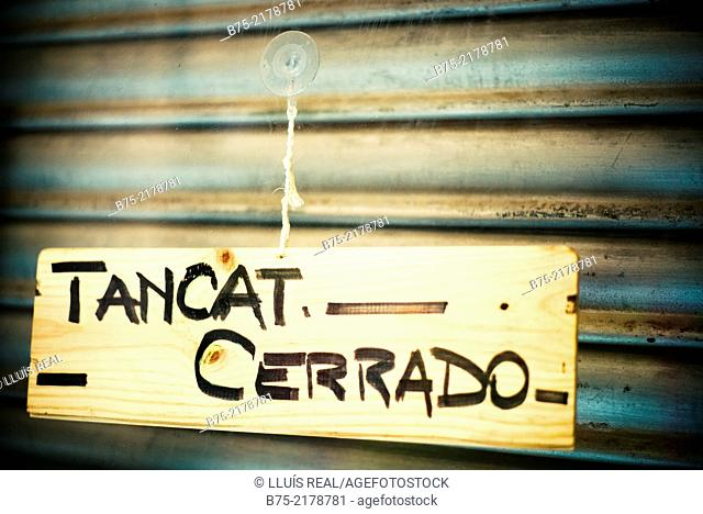 Door of a business with a closed 'tancat-cerrado' sign. Barcelona, Spain, Europe