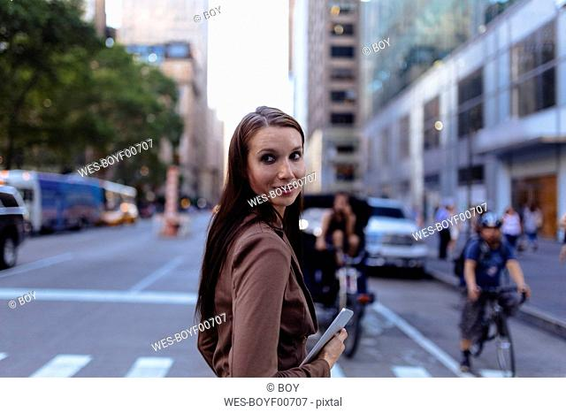 USA, New York, Manhattan, portrait of young businesswoman with tablet crossing the street