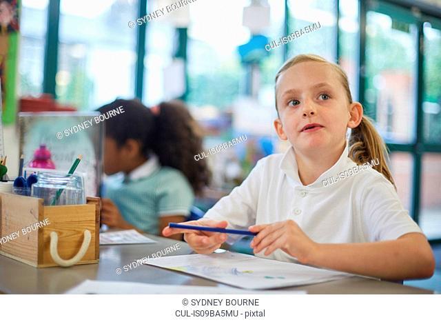 Schoolgirl looking up in classroom lesson at primary school