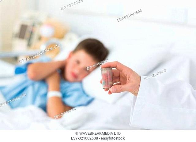 Doctor holding pill bottle with boy in hospital