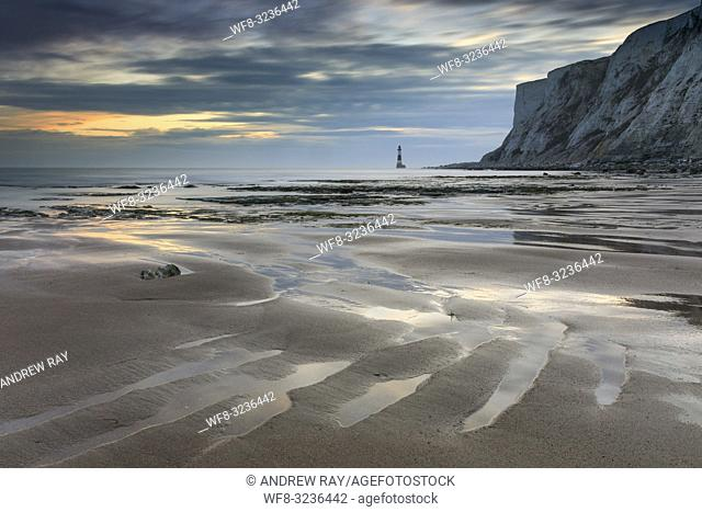 Sand ripples on Falling Sands Beach in East Sussex captured at sunset in early March with Beachy Head and Beachy Head Lighthouse in the distance