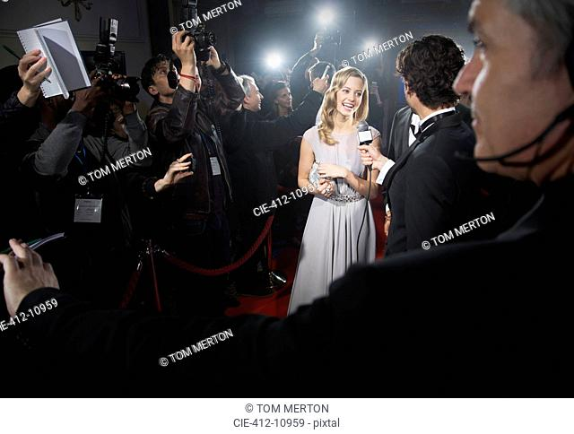 View over bodyguard's shoulder of celebrity being interviewed on red carpet