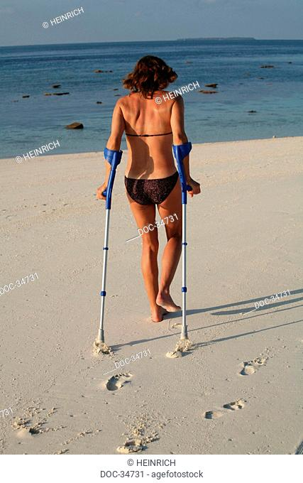 woman from the backside dressed with a bikini going fŸr a walk with crutches at the beach