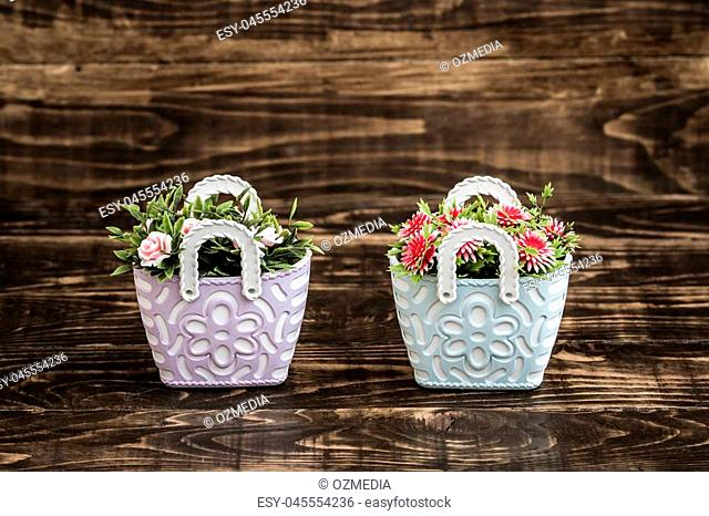 Artificial flowers in colorful flowerpots on brown wooden background