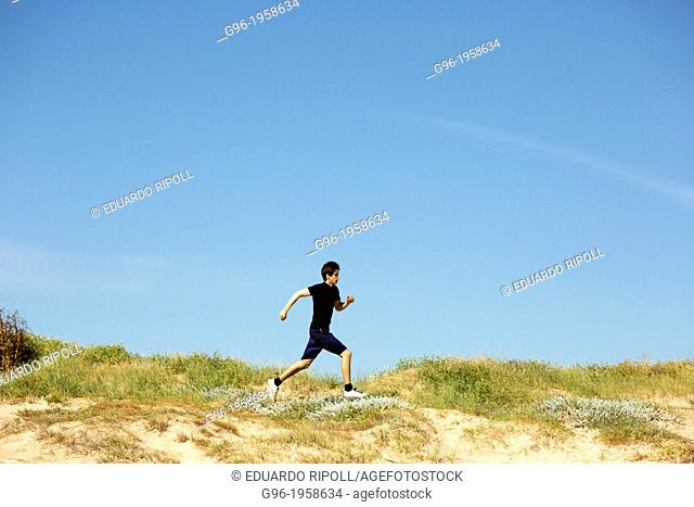 Young adult running in the dunes