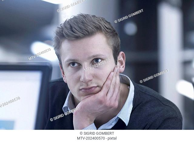 Young businessman thinking and working till late night in office, Freiburg im Breisgau, Baden-Württemberg, Germany