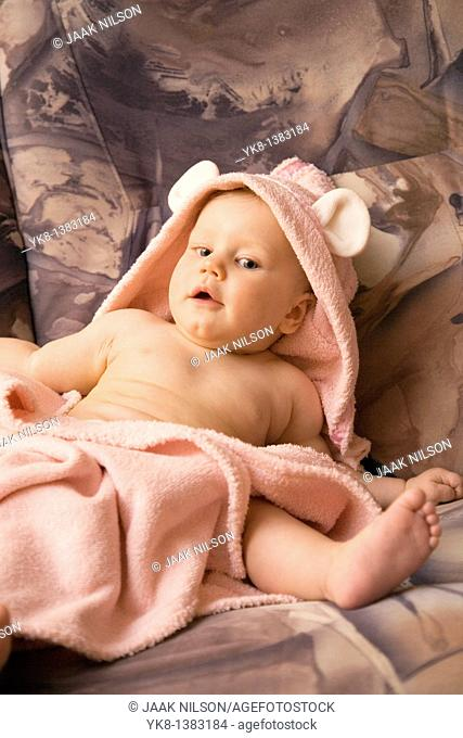 Happy Emotional Eight Month Old Infant Girl Sitting in Bathrobe