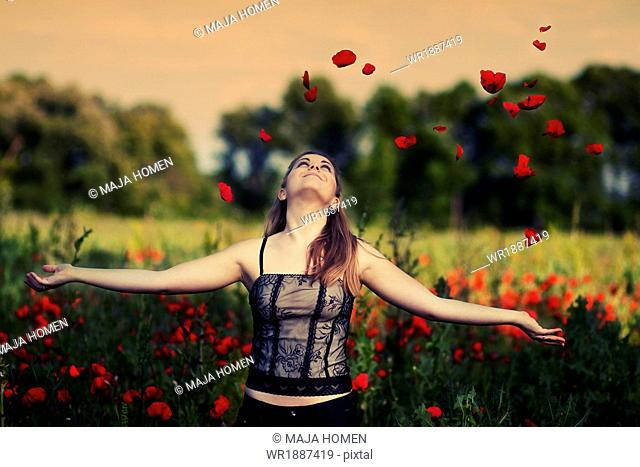 Young woman playing with poppies in a poppy field, Croatia, Europe
