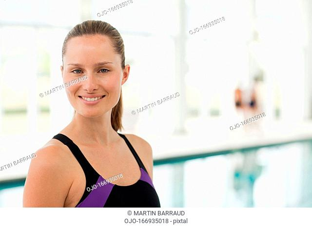 Portrait of smiling woman standing at swimming pool