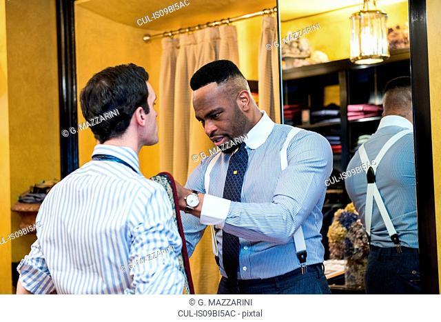 Tailor fastening customer's tie in tailors shop