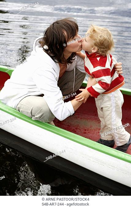 Mother and son 2-3 years in a canoe kissing