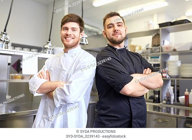 happy smiling chef and cook at restaurant kitchen