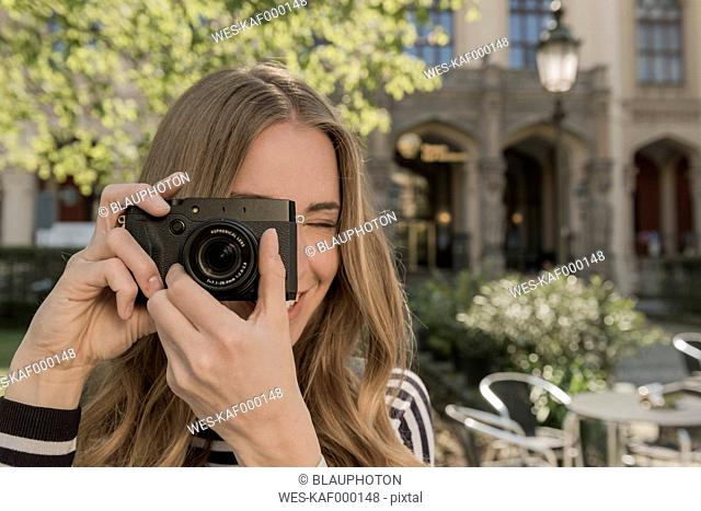 Smiling young woman taking a picture